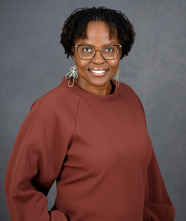 Angela Patton, smiling Black woman looking at camera, wearing glasses