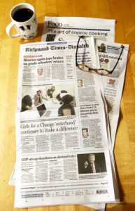 Newspaper cover page, cup of coffee and glasses lying on top of it
