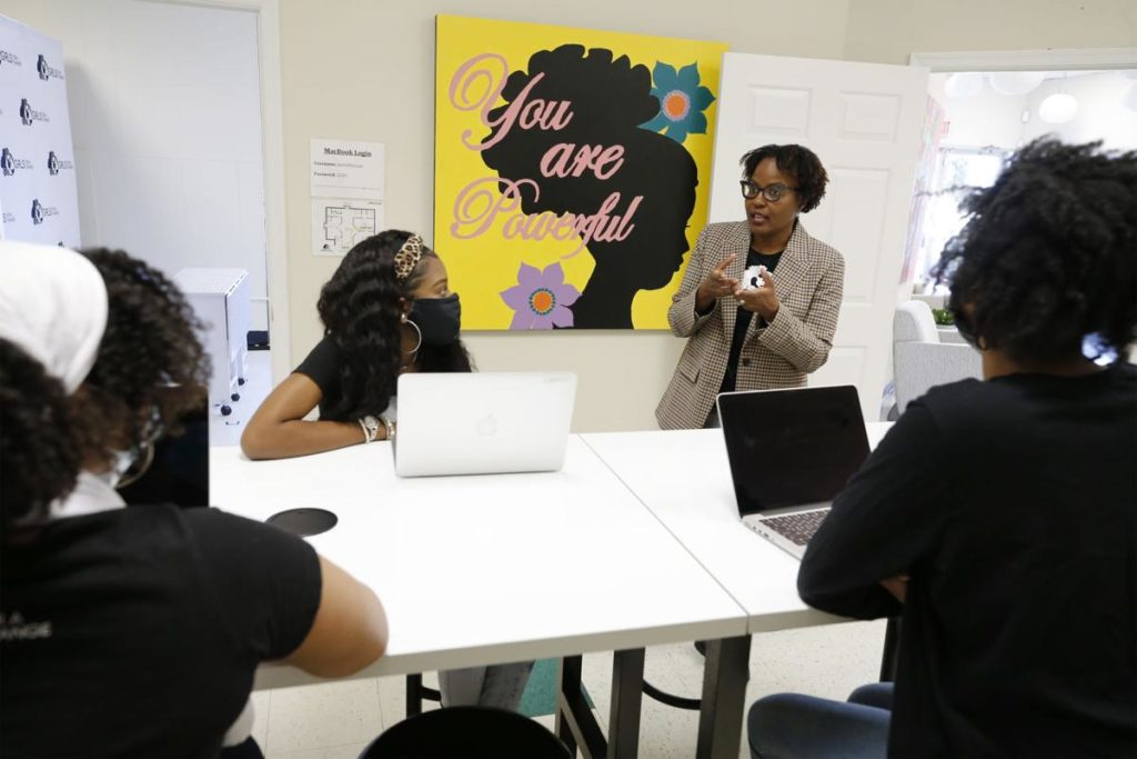 Smiling Black woman speaking to two Black girls in a technology lab