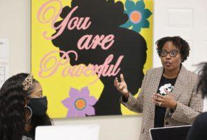 Smiling Black woman speaking to two Black girls