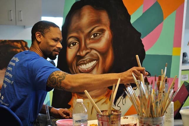 Hamilton Glass painting an image of a smiling Black woman
