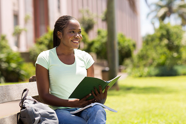 Black girl on a college campus studying on a park bench