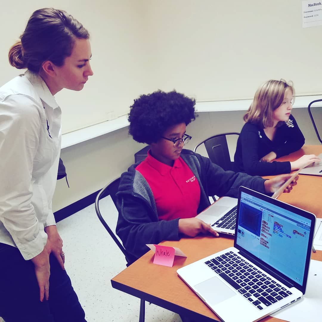 teacher in classroom with girls coding on laptops
