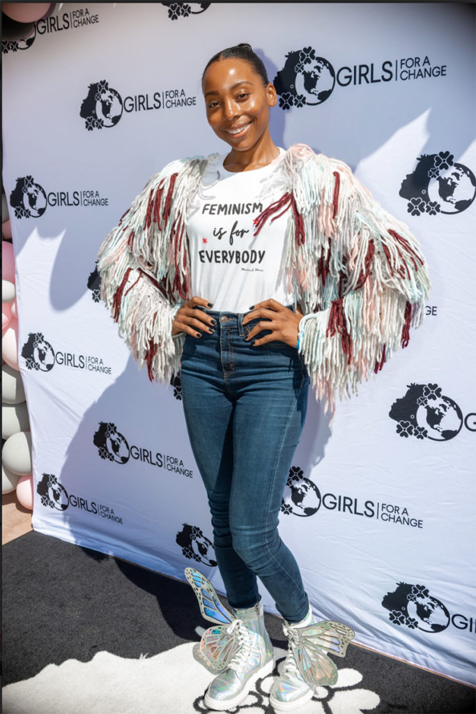 Erica Ash, smiling in front of a Girls For A Change banner