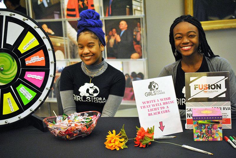Happy Black girls sitting at a vendor table together