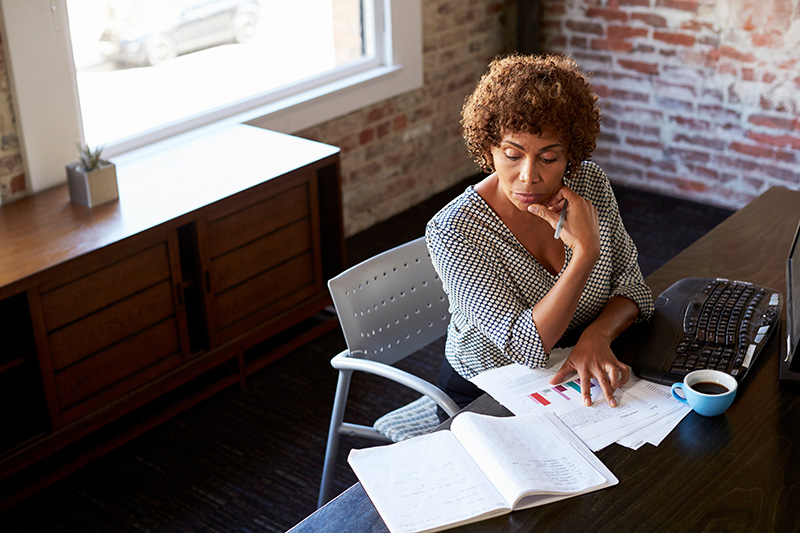 Black woman looking at data for grant writing